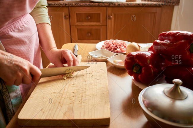 Unrecognizable concentrated senior female in apron cutting garlic while preparing ingredients for stuffed peppers