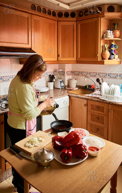 Side view of elderly housewife in apron standing in kitchen and pouring oil in frying pan for preparing tasty dinner