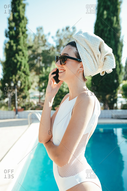 Side view of calm female in swimsuit standing near pool and speaking on smartphone during sunny day