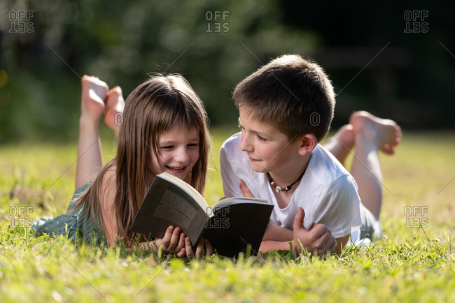 Carefree preteen siblings in summer outfit lying on green grass and enjoying interesting book while spending weekend in park