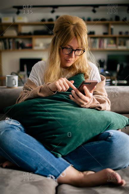 From above anonymous female sitting with cushion at home and surfing cellphone during weekend