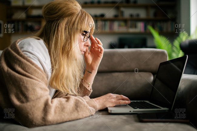 Side view of serious female freelancer in eyeglasses lying on sofa in living room and browsing netbook while working on project