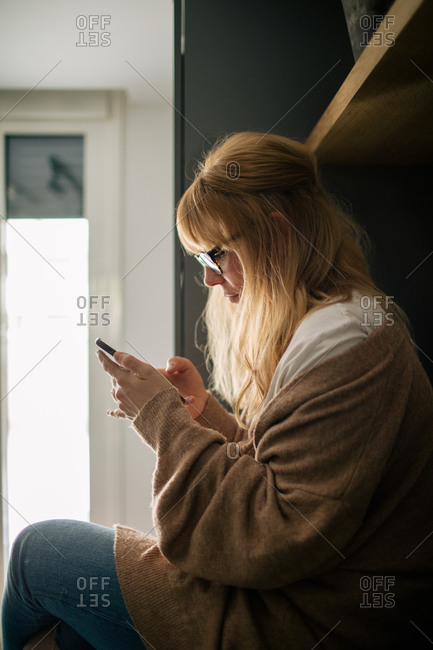 Side view of serene female in cozy clothes sitting on counter in kitchen and reading messages on social media