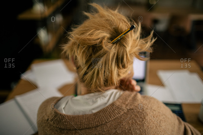 Back view of female freelancer with pencil in hair sitting at table in home office and working remotely while reading documents and using laptop