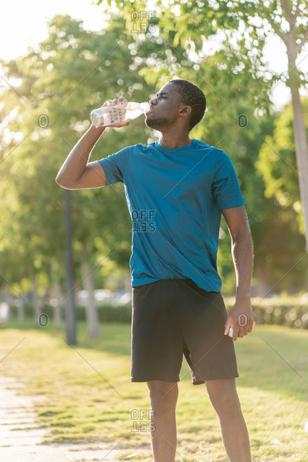 African athletic black man in sport clothes drinking water from a bottle at sunset