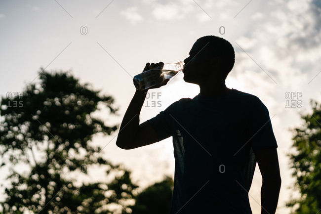 Silhouette of african athletic black man in sport clothes drinking water from a bottle against sky at sunset