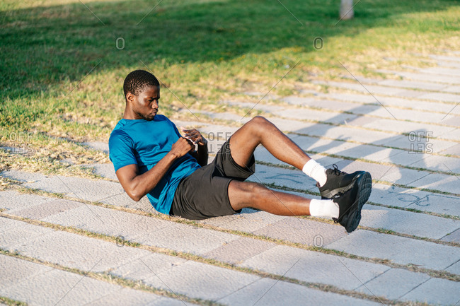 African black man doing abdominal crunch exercises on the floor on a sunny day in the park