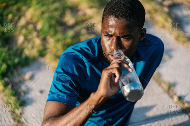 African athletic black man in sport clothes sitting down and drinking water from a bottle at sunset