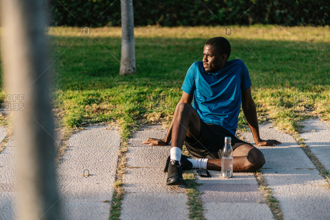 African athletic black man in sport clothes sitting down and looking away at sunset