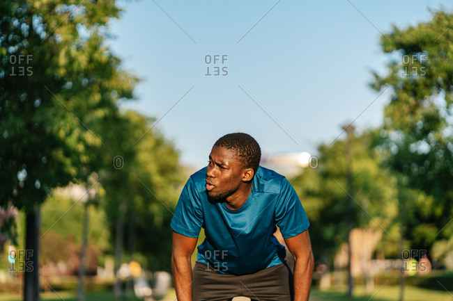 Close up of exhausted african black man resting in the park at sunset after working out