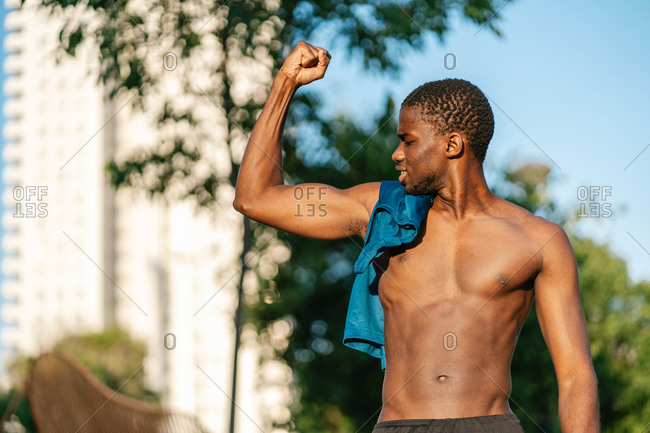 African athletic shirtless black man flexing arm in the park on a sunny day