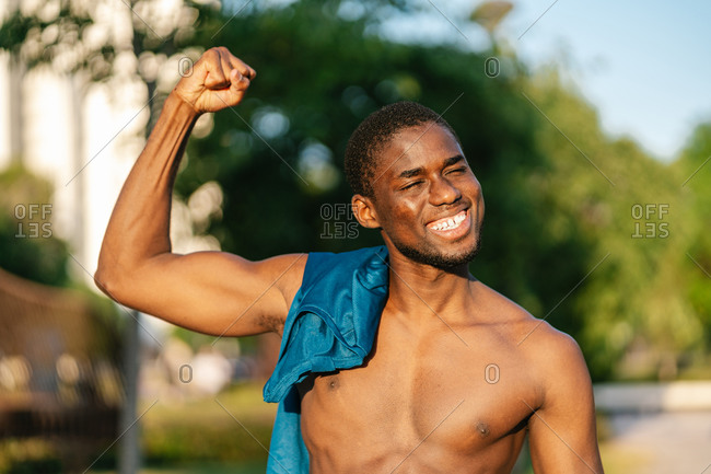 African athletic shirtless black man in sport clothes flexing arm and smiling in the park on a sunny day