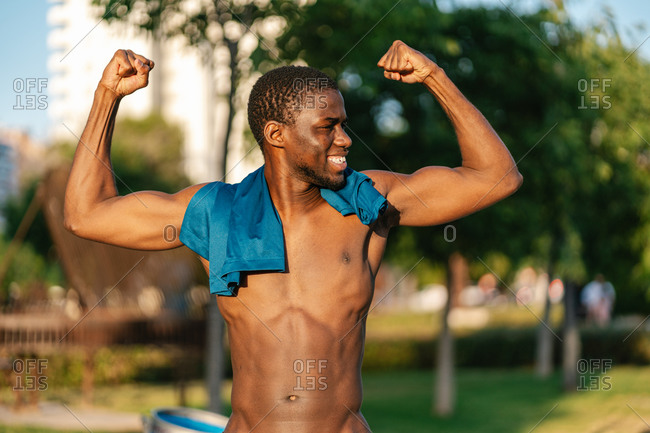 African athletic shirtless black man in sport clothes flexing arms and smiling in the park on a sunny day