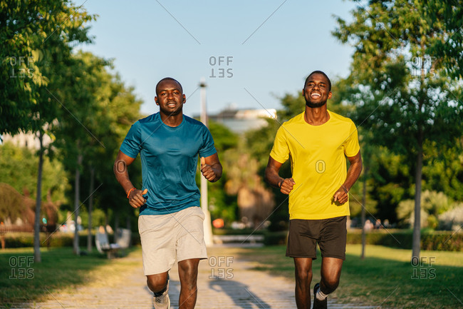 Two athletic black men wearing colorful sport clothes running in the park on a sunny day
