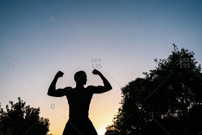Silhouette of african athletic black man in sport clothes flexing arms against sky at sunset
