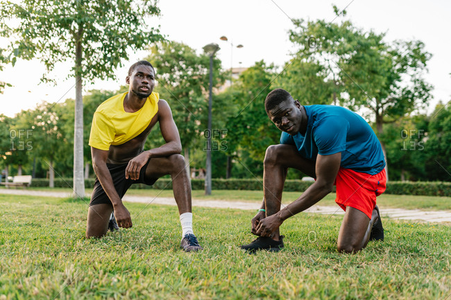 Two athletic black men wearing colorful sport clothes kneeling down resting after running in the park on a sunny day