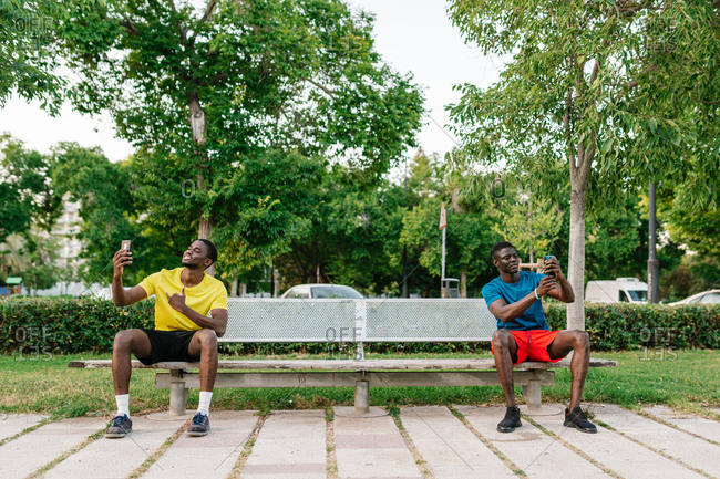 Two athletic black men wearing colorful sport clothes sitting down on bench respecting social distancing and using their phones