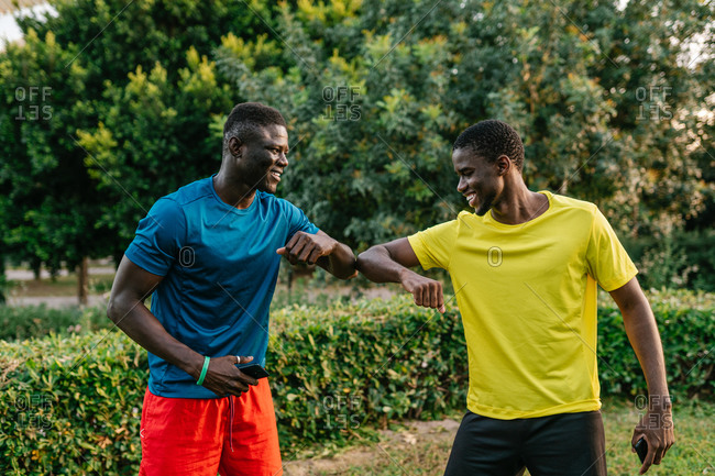 Two black men in colorful sport clothes greeting doing the elbow bump outdoors in the park
