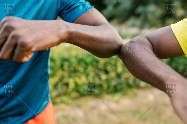 Close-up of two anonymous black men doing the elbow bump outdoors in the park