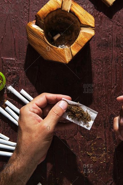 Unrecognizable male smoker making marijuana joint