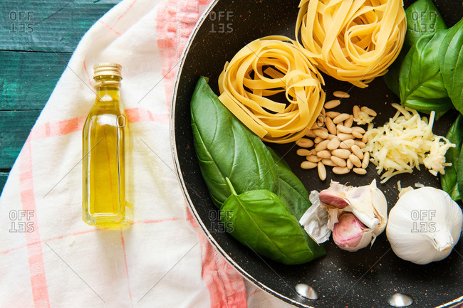 Top view of bottle of olive oil near frying pan with raw tagliatelle rolls surrounded by heads of garlic with green basil leaves and crispy pine nuts