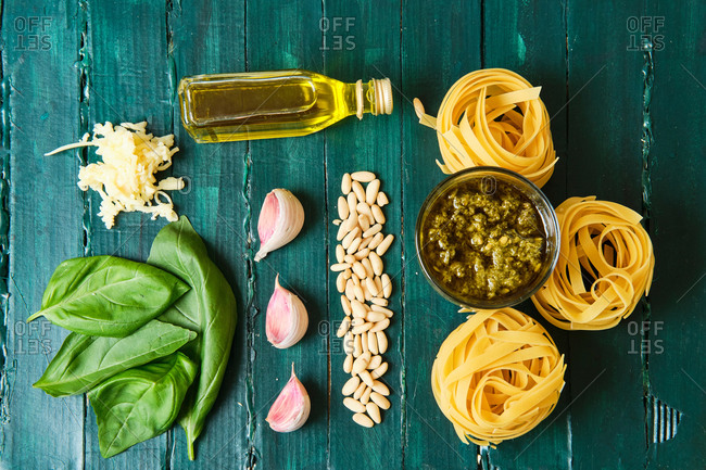 Top view of composition of dry pasta rolls near bowl with pesto sauce and fresh basil leaves with crushed garlic and pine nuts near bottle with olive oil