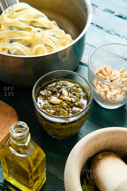 From above of glass bowl with yummy pesto sauce near pot with cooked pasta and bottle of olive oil near mortar and pestle
