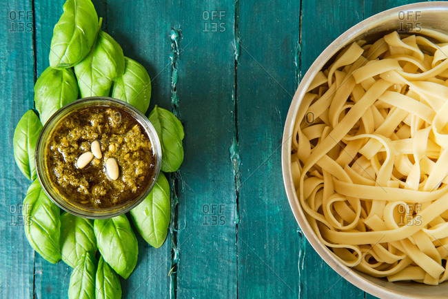 Top view of small glass bowl with famous Italian pesto sauce made of fresh basil leaves and pine nuts covered with olive oil near of delicious Italian pasta