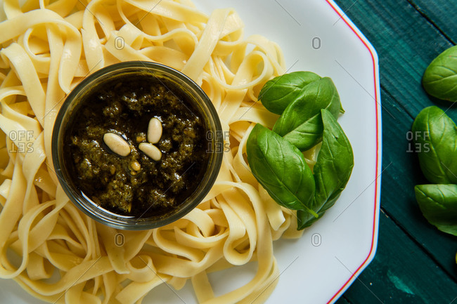 From above of yummy tagliatelle with Italian pesto sauce on top decorated with crunchy pine nuts and fresh basil leaves