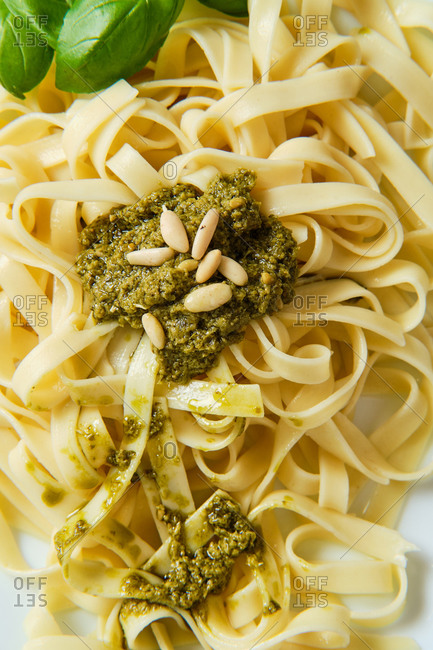 From above of yummy tagliatelle with Italian pesto sauce on top decorated with crunchy pine nuts and fresh basil leaves in cafe