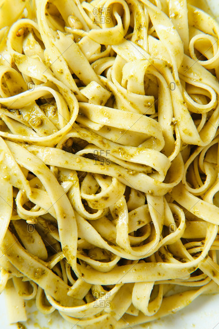From above of yummy tagliatelle with Italian pesto sauce with crunchy pine nuts and fresh basil leaves