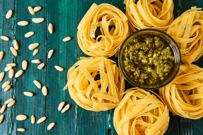From above of tasty pesto salsa with olive oil surrounded by uncooked pasta rolls and spilled crunchy pine nuts on wooden table
