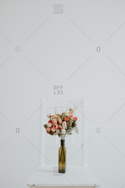 Vintage bridal flower bouquet placed inside a glass vase placed on a white wooden chair in an empty room with white walls