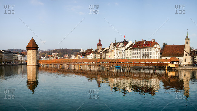 Amazing landscape of river and old Chapel Bridge with tower against blue sky in Lucerne