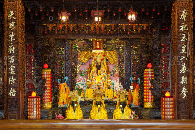 Oriental temple with ornamental altar surrounded by walls and columns decorated with gold in Taipei