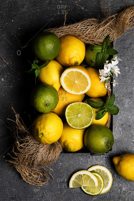From above view still life of limes and lemons basket placed on dark textured surface