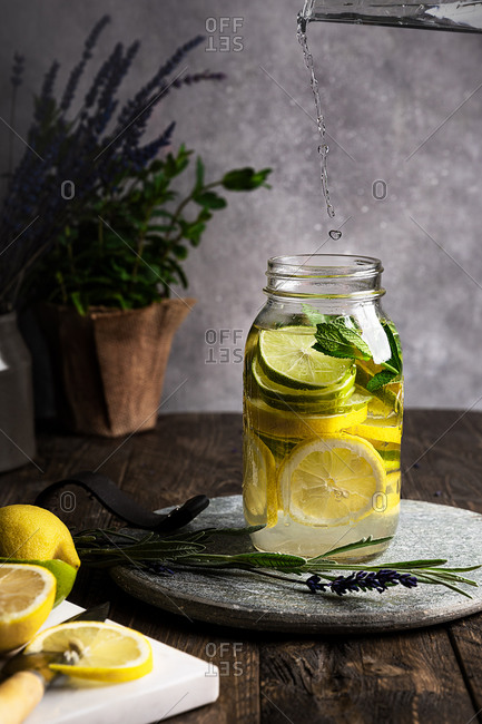 Side view still life of lemonade in a glass jar, placed on a wooden table