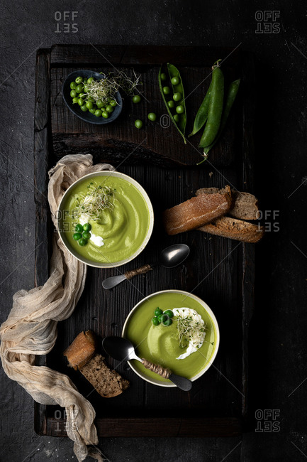 From above view of two bowls of pea cream placed on a wooden tray and dark surface, served with bread and decorated with whole peas and sour cream
