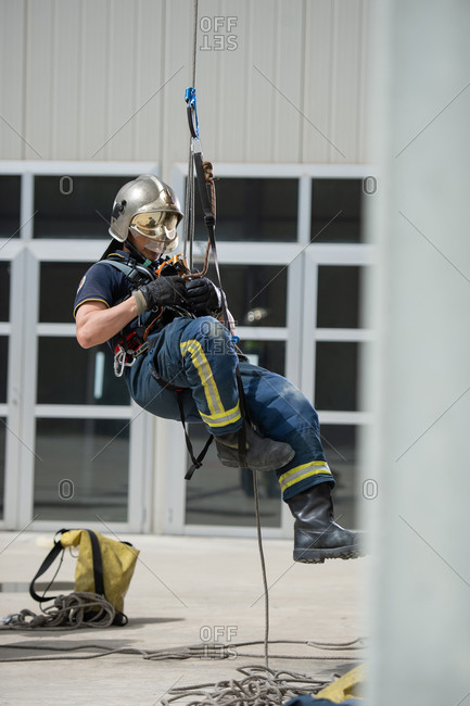 Side view of strong firefighter in protective equipment during training with ropes near building