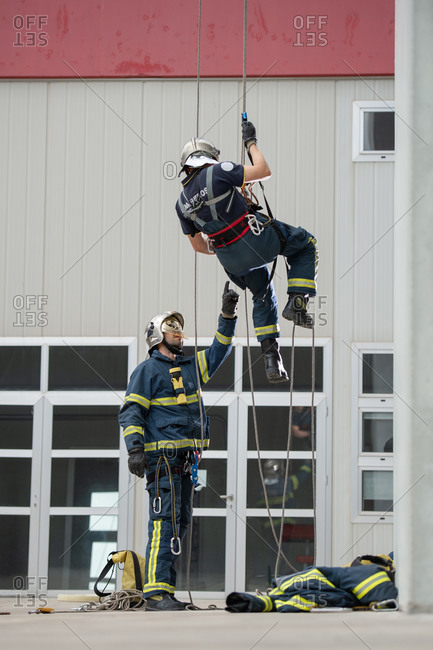 Brave fireman climbing rope under control of skilled male colleague near building in training center