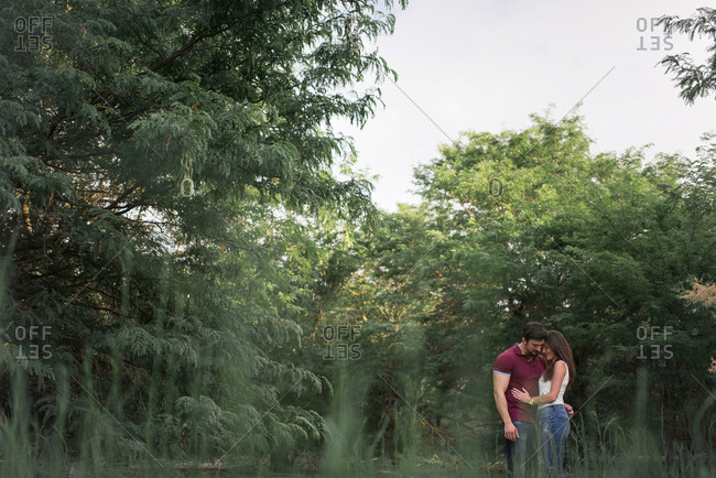 Side view of tender couple embracing each other while standing in garden on sunny day