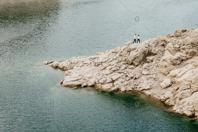 From above of distant couple of unrecognizable travelers walking on rough rocky hill on seashore with rippled sea water