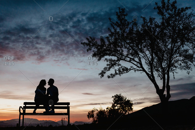 Back view silhouettes of affectionate couple enjoying romantic date while sitting on bench against cloudy sunset sky in summer evening
