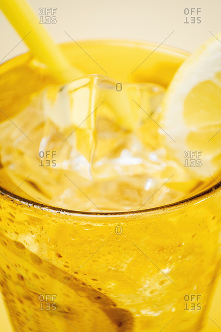 From above crop detail of glass of fresh beverage with lemons and kiwi placed in yellow background in studio