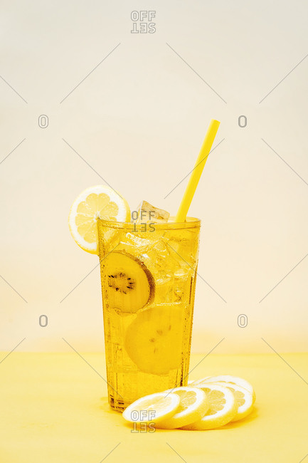 Glass of fresh beverage with lemons and kiwi placed on table in studio