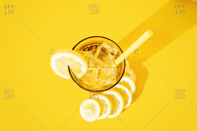 From above glass of fresh beverage with lemons and kiwi placed on table in studio