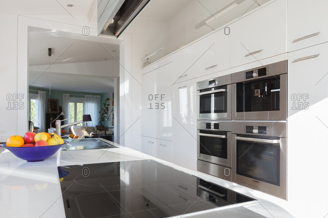 Interior of contemporary kitchen with high tech furniture and appliances in apartment during daytime