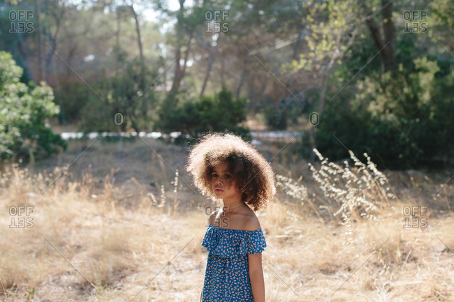 Side view focused mulatto girl in back lit with curly hair wearing blue dress with open shoulders standing in rural location against green trees on sunny day