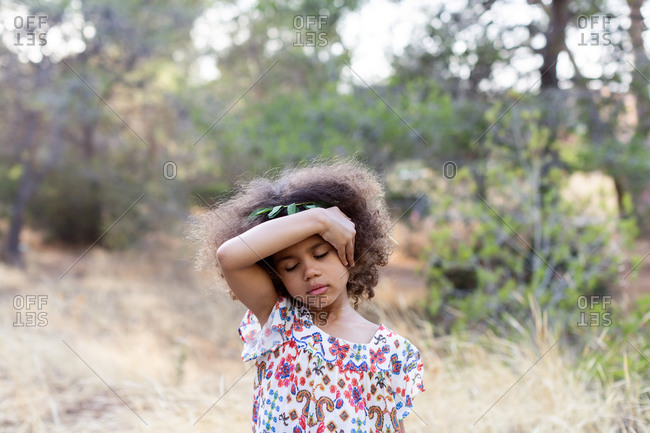 Portrait of adorable calm ethnic girl wearing stylish colorful dress while spending summer day in nature