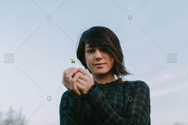 From below charming female in trendy wear standing with rose flower in green meadow and looking at camera